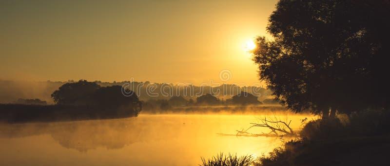 村庄的房子的不同的等高在黎明早晨的大雾淹没在明亮的 库存照片