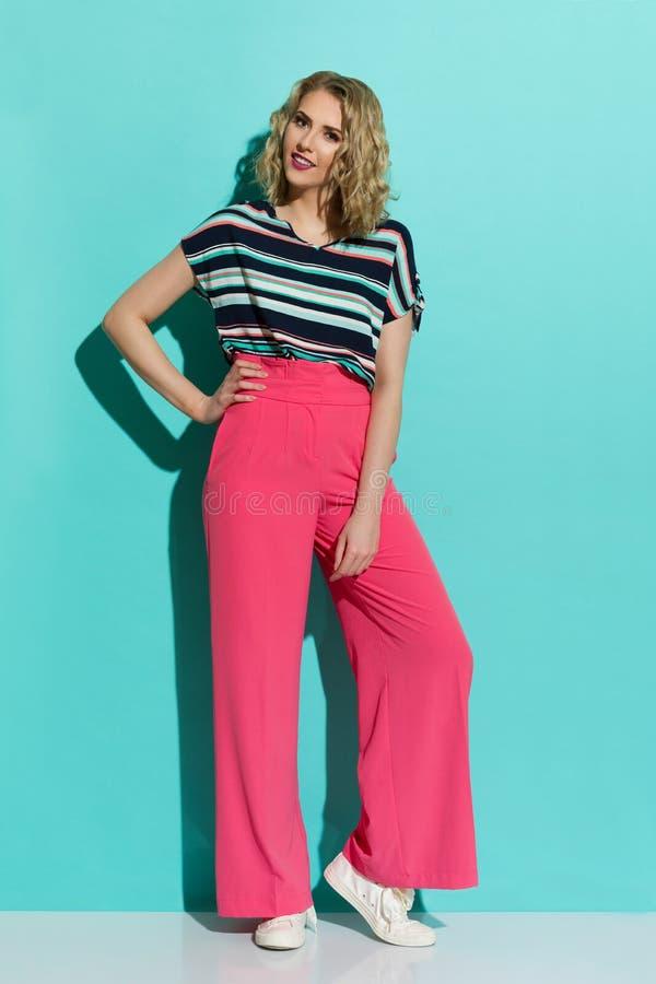 桃红色宽腿长裤、运动鞋和镶边女衬衫的时髦的妇女 免版税库存照片