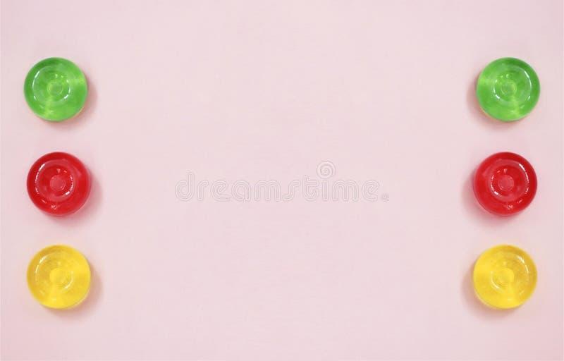 桃红色抽象背景有在五颜六色的糖果的顶视图 图库摄影