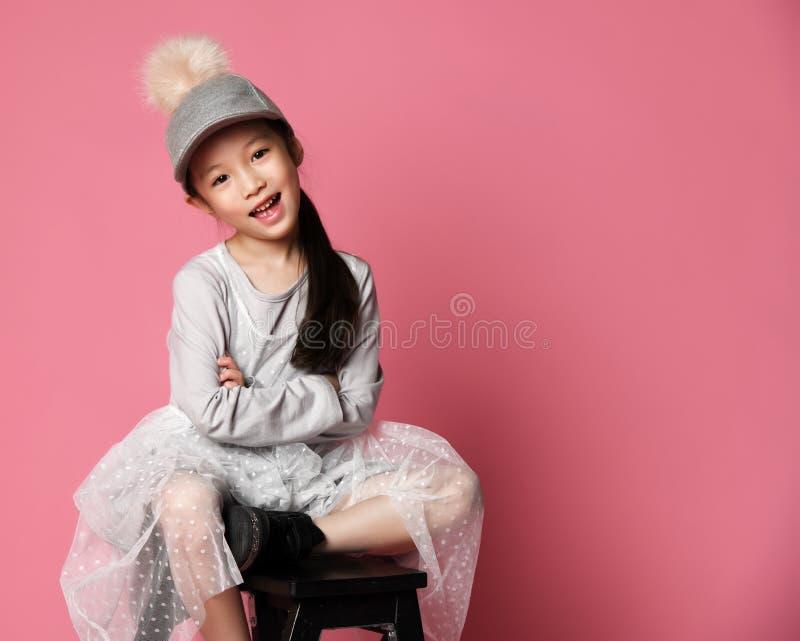 桃红色礼服和滑稽的盖帽的恰好微笑的亚裔时尚孩子女孩有毛皮绒球的 免版税库存图片