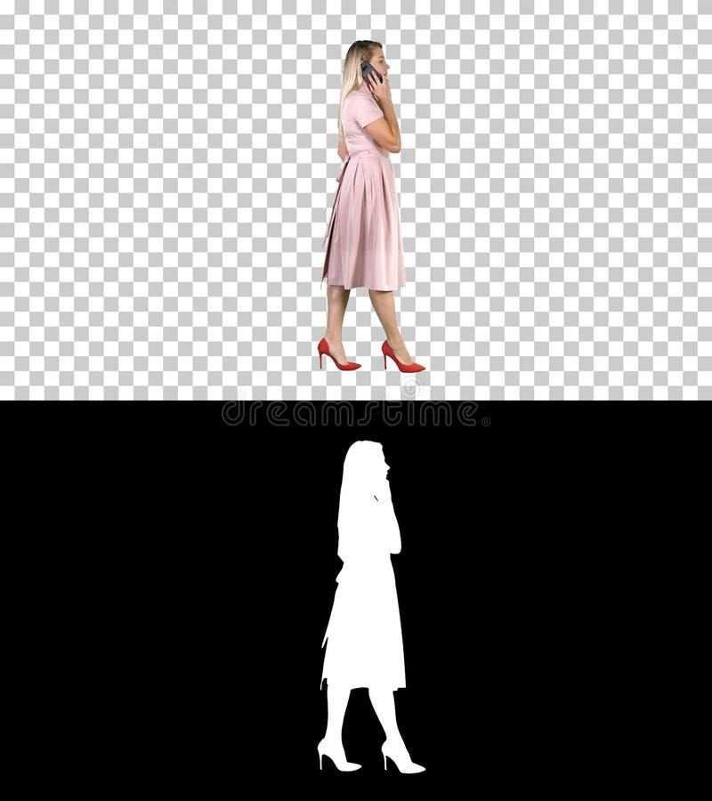 桃红色礼服的妇女谈话在电话,阿尔法通道 库存照片