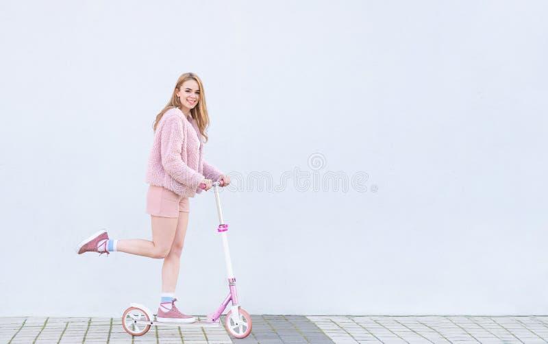 桃红色衣裳乘驾的女孩在一辆桃红色反撞力滑行车,调查照相机和微笑,隔绝在白色背景 库存图片