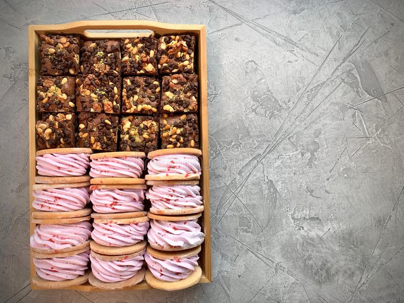 桃红色蛋白软糖和果仁巧克力在一个木箱 在一个灰色背景 免版税库存图片