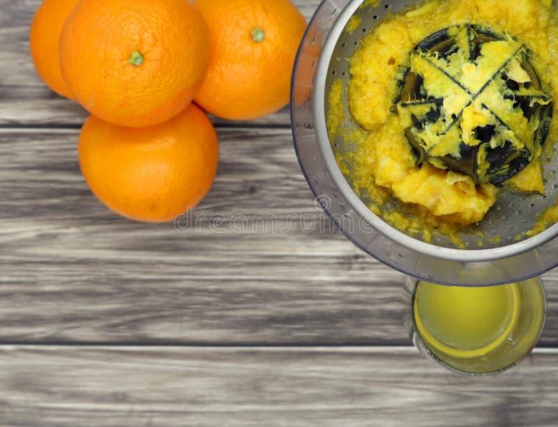 桔子、榨汁器和一杯顶视图在木背景,拷贝空间的汁液 库存照片