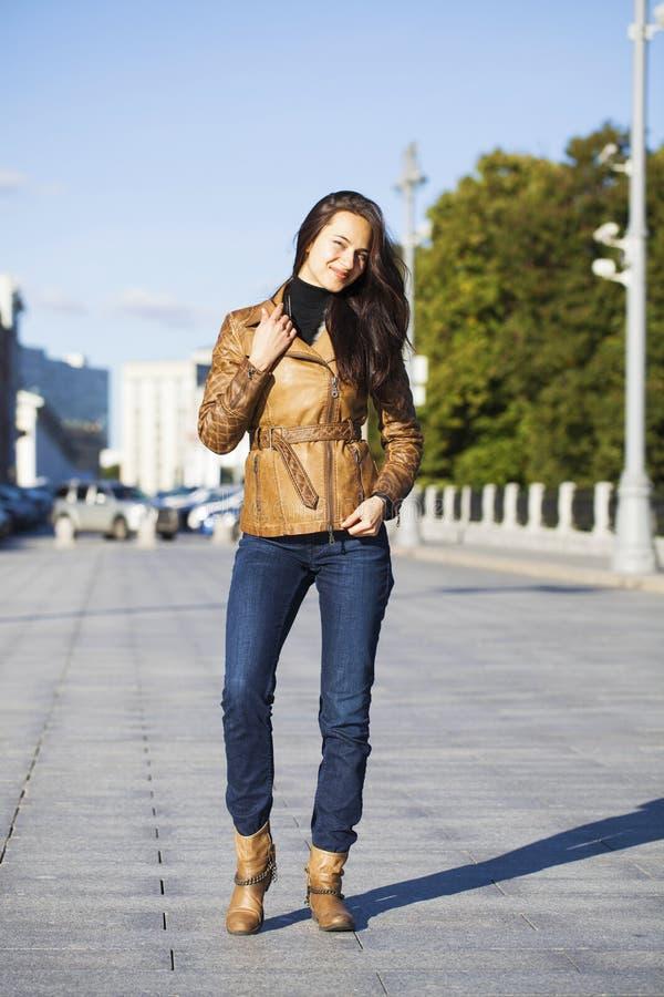 棕色皮夹克的年轻愉快的妇女 免版税图库摄影