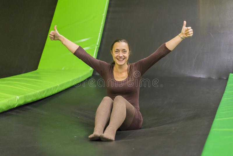 棕色适合的礼服的年轻女人在绷床在绷床中心 垂直的照片 绷床的愉快的女孩 愉快的年轻女人  免版税图库摄影