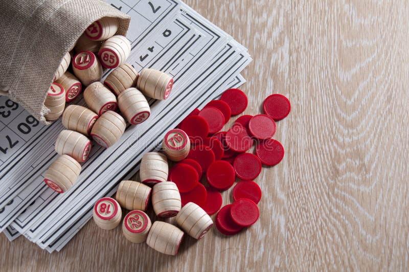 棋乐透纸牌 乐透纸牌比赛的卡片在他们的木桶和红色芯片溢出在袋子外面 小组娱乐, 库存照片