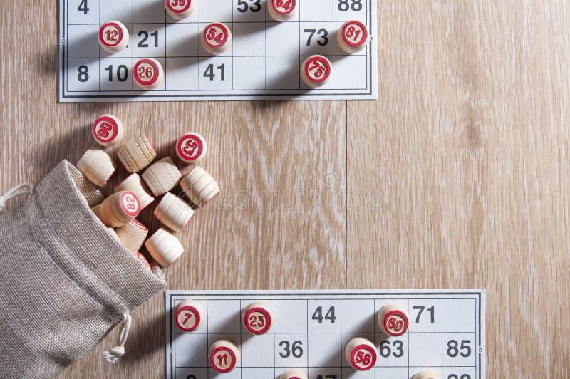 棋乐透纸牌 木乐透纸牌滚磨与袋子和游戏卡一场比赛的在乐透纸牌 木背景 小组娱乐,家庭 免版税库存照片