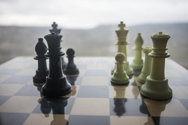 棋盘企业想法和竞争和战略想法的比赛概念 在棋枰室外日落的棋形象 免版税库存图片