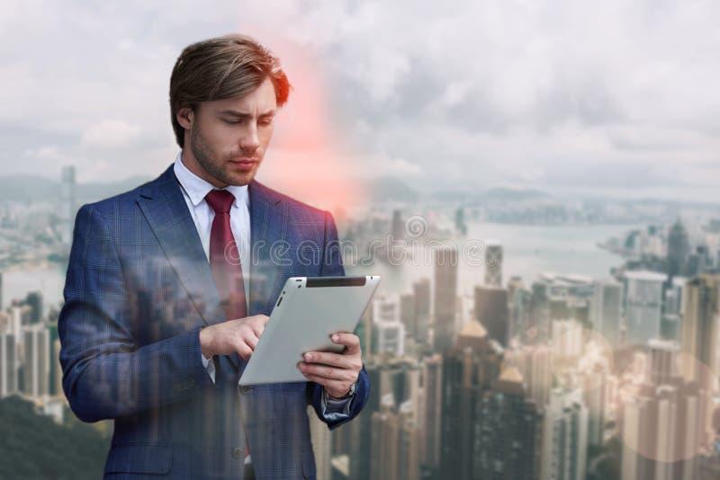 检查他的邮件 在衣服的英俊的有胡子的商人使用数字片剂,当站立反对都市风景时 库存照片
