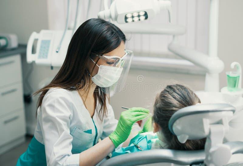 检查女孩患者的女性牙医在牙齿诊所 库存照片