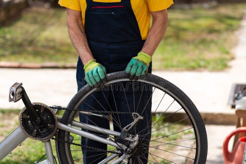 检查自行车轮胎气压的人 库存图片
