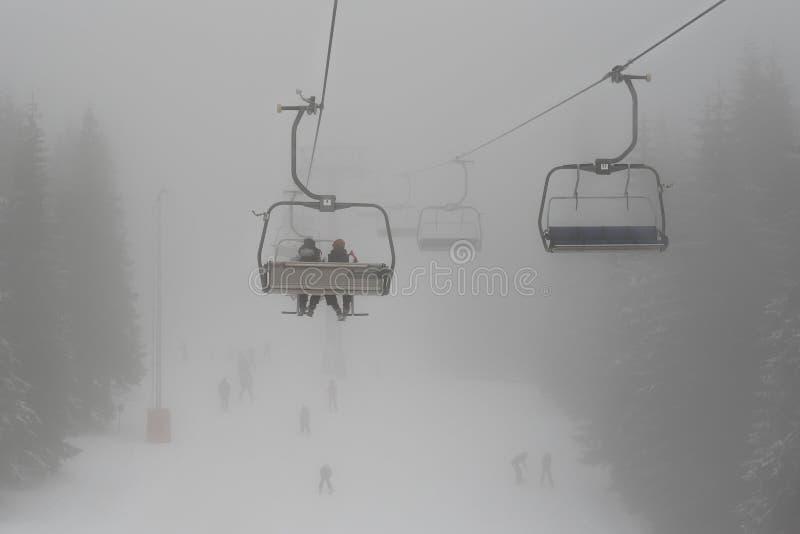 椅子与滑雪者剪影的滑雪电缆车在深薄雾 免版税库存图片