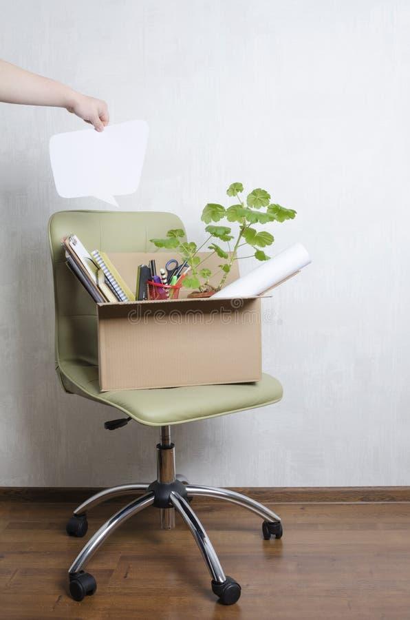椅子和箱子有另外材料的在它,拿着空白的讲话泡影您的文本的男性手 /被射击的概念移动从工作 免版税库存图片