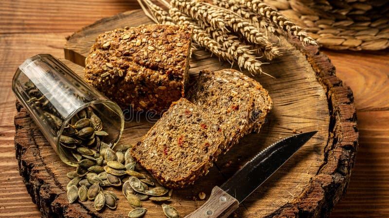 概念吃健康 与goji莓果,南瓜种子的整个五谷面包,在木背景的一块板材 图库摄影