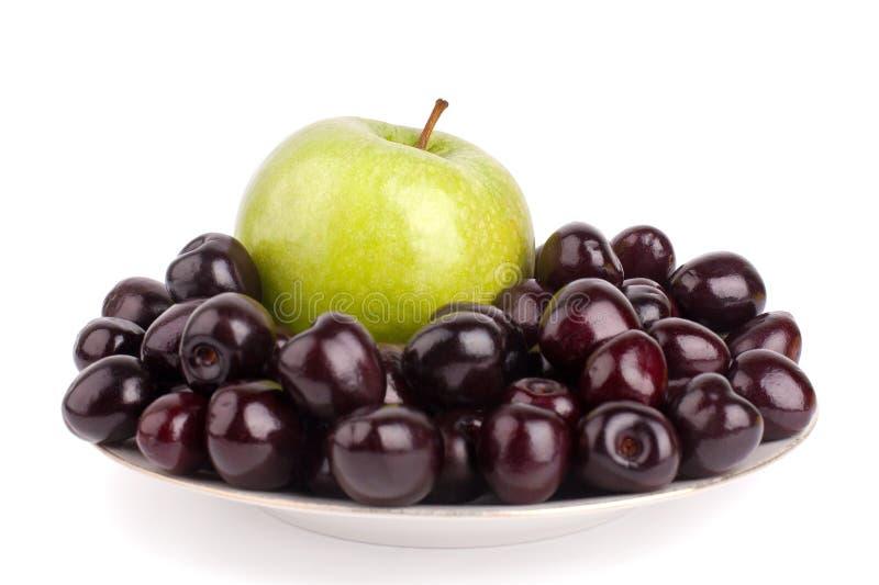 樱桃莓果和一个大绿色苹果在白色板材白色背景被隔绝的关闭宏指令 免版税库存照片