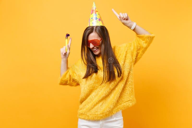 橙色滑稽的玻璃生日宴会帽子的快乐的妇女有演奏的管子上升的手指向食指的  免版税库存图片