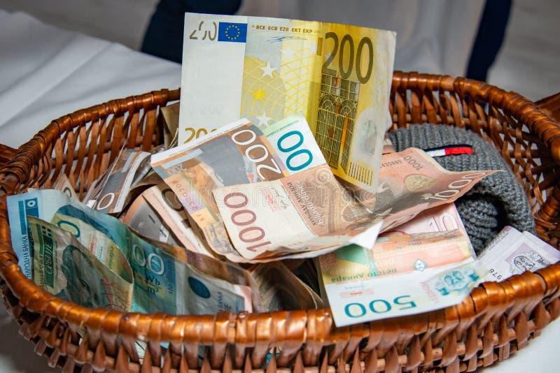 欧元和塞尔维亚丁那钞票在篮子 库存图片
