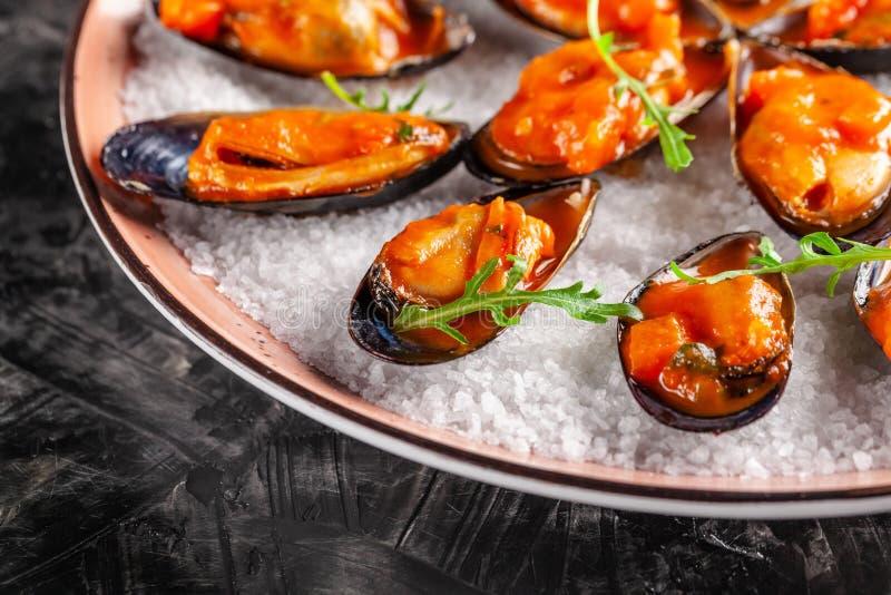欧洲烹调 在西红柿酱的用卤汁泡的淡菜用迷迭香,大蒜,辣椒 大盘子在板材的餐馆 库存图片