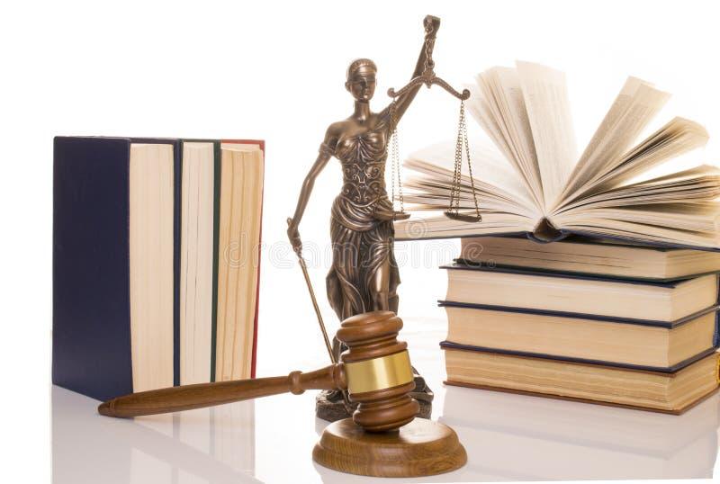 正义,在书后的法官的锤子雕象在白色背景 免版税库存图片