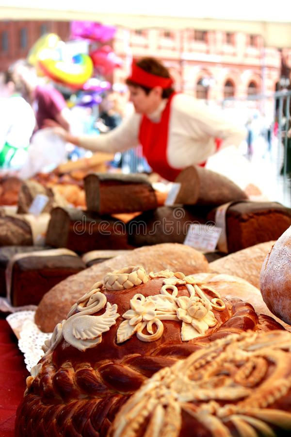 正方形的面包妇女卖主与圆的大面包,面包特写镜头  库存图片