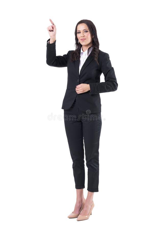 正装的年轻愉快的美丽的典雅的女商人指向手指的  库存照片