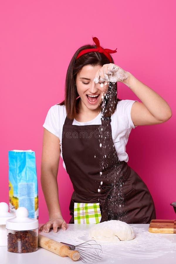 正面主妇佩带头饰带和围裙,做可口酥皮点心的面团,揉并且用面粉,在厨房用桌附近站立 库存照片