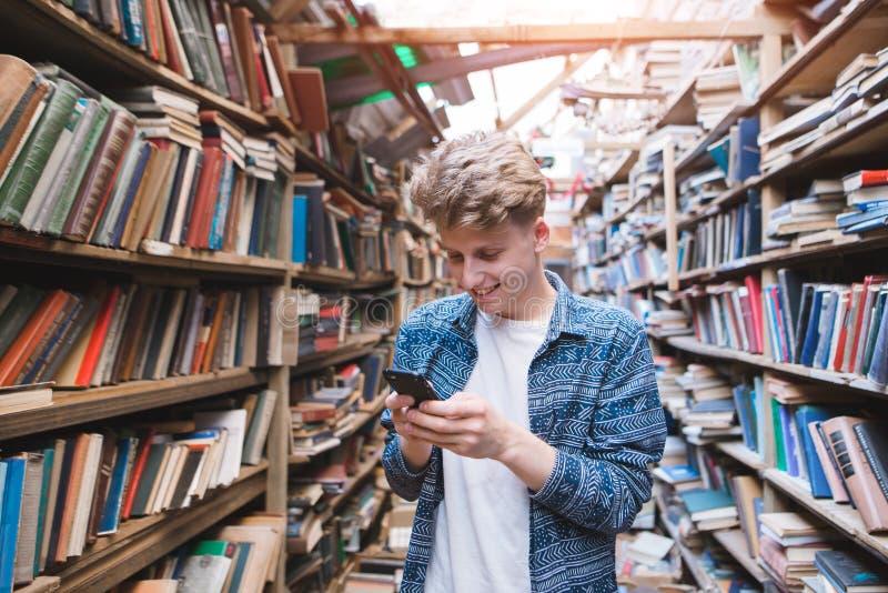 正面年轻人在一个公立图书馆和微笑使用一个智能手机 库存照片