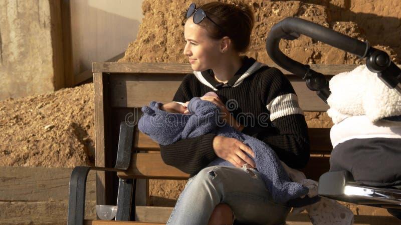 正面和微笑的妈妈哺养的婴孩室外在有的长凳休息 库存图片