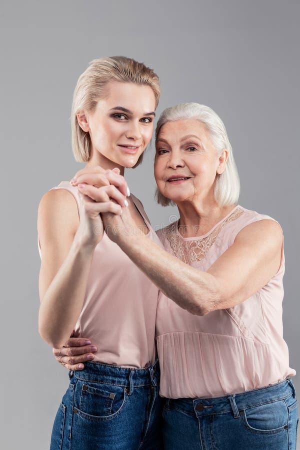 正面高白肤金发的女孩连接的手和身体有老妇人的 免版税库存图片