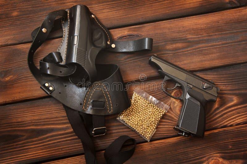 武器 枪和手枪皮套一把手枪的在木背景 免版税库存图片