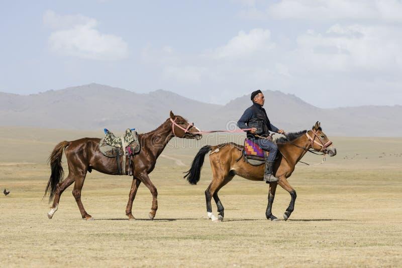 歌曲Kul,吉尔吉斯斯坦, 2018年8月8日:吉尔吉斯乘驾他的马和主角别的在皮带在歌曲Kul湖在吉尔吉斯斯坦 免版税库存照片