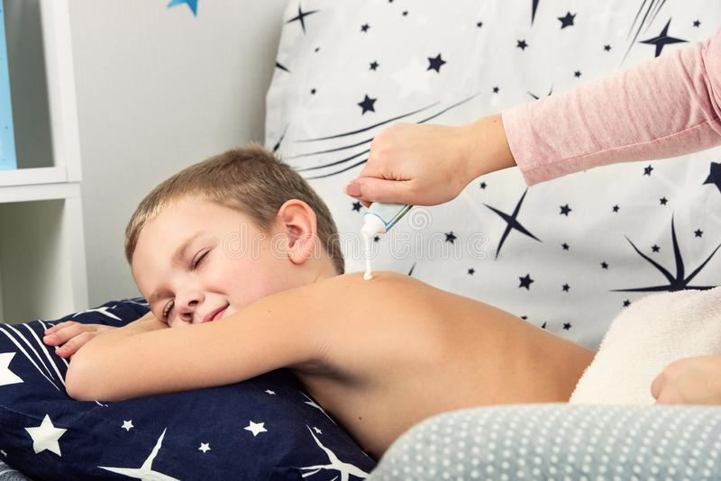 母亲做按摩他的小儿子后面  她抹上她的后面与奶油 免版税库存照片