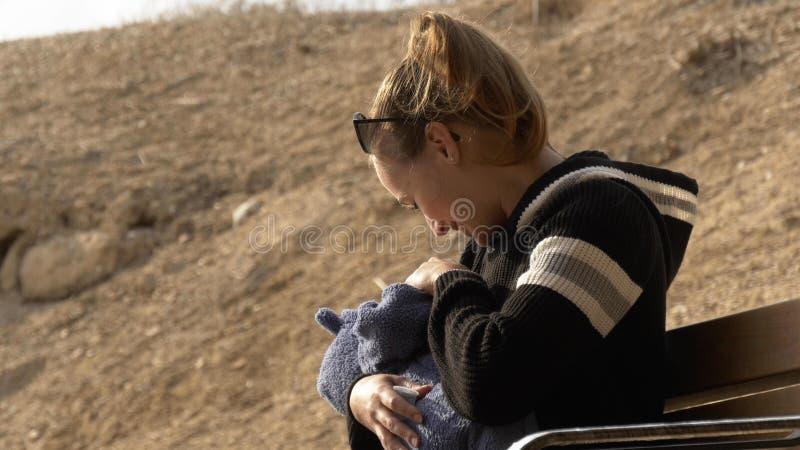 母亲微笑和谈话与室外小的婴孩 免版税库存图片