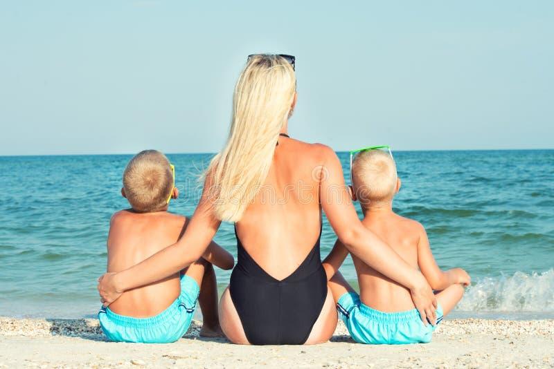 母亲和两个儿子坐沙子并且看海 我其他看到暑假工作 图库摄影