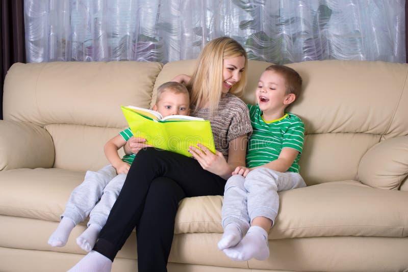 母亲和两个儿子读一本书 库存照片