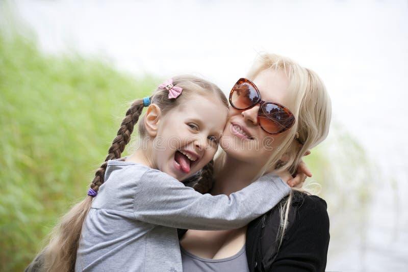 母亲和一点女儿微笑 免版税库存照片