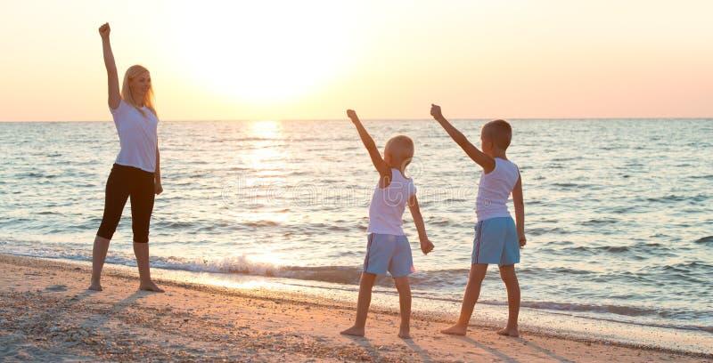 母亲和孩子做在海滩的锻炼,他们遇见日出 健身、体育、瑜伽和健康生活方式概念 免版税库存图片