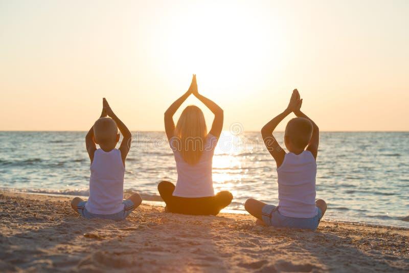 母亲和孩子做在海滩的锻炼,他们遇见日出 健身、体育、瑜伽和健康生活方式概念 免版税库存照片