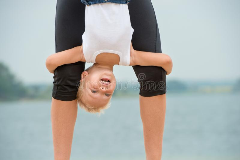 母亲和儿子做着在海滩的锻炼 体育休闲 免版税库存照片