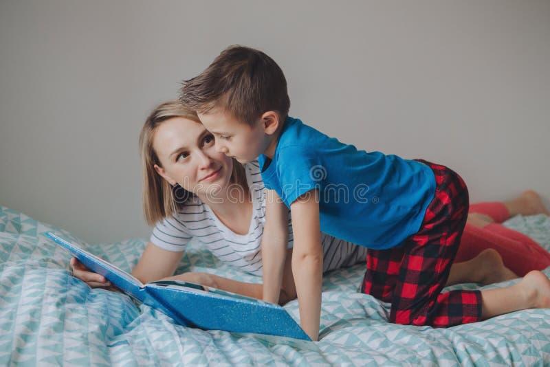 母亲和男孩儿子在家看书 免版税库存照片