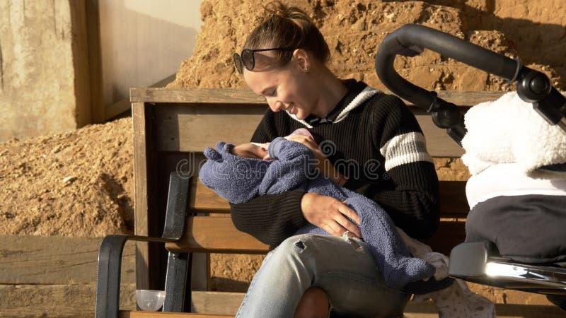 母亲喂养她的在坐之外的可爱宝宝在banch在城市公园 免版税库存图片