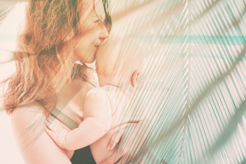 母亲抱着手防护湿气的婴孩 库存照片