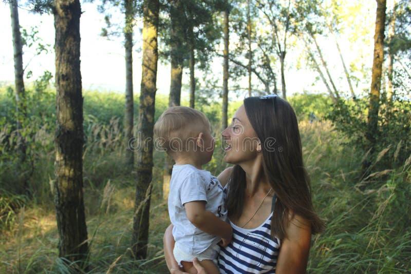 母亲节快乐妈妈和儿子杉木森林妈妈的和儿子微笑着并且拥抱 家庭假日和交往 库存图片