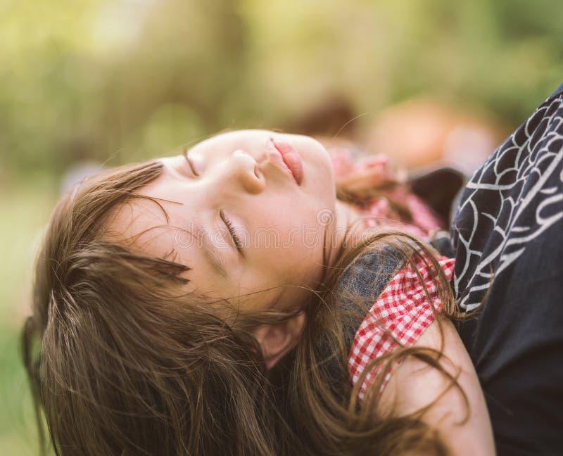 母亲肩膀的睡觉的女孩在自然公园 库存图片