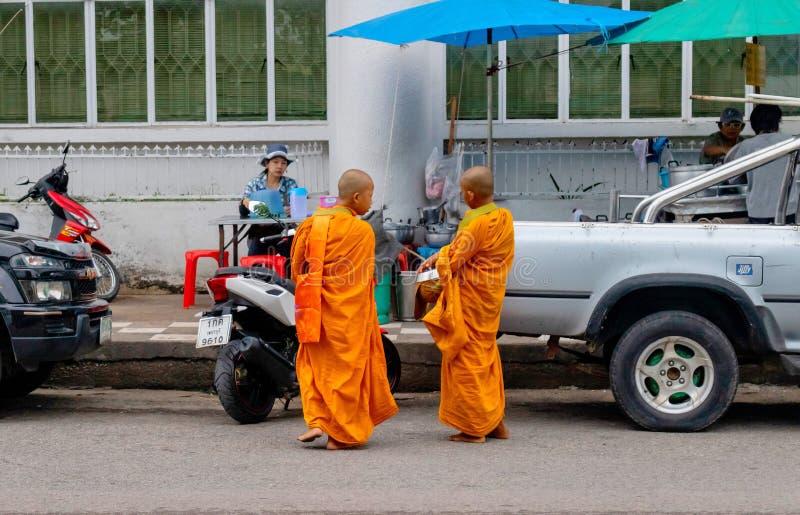 每天早晨,两名小修士一起谈话,当走动在Pranburi市,泰国2017年时6月10日 免版税库存照片