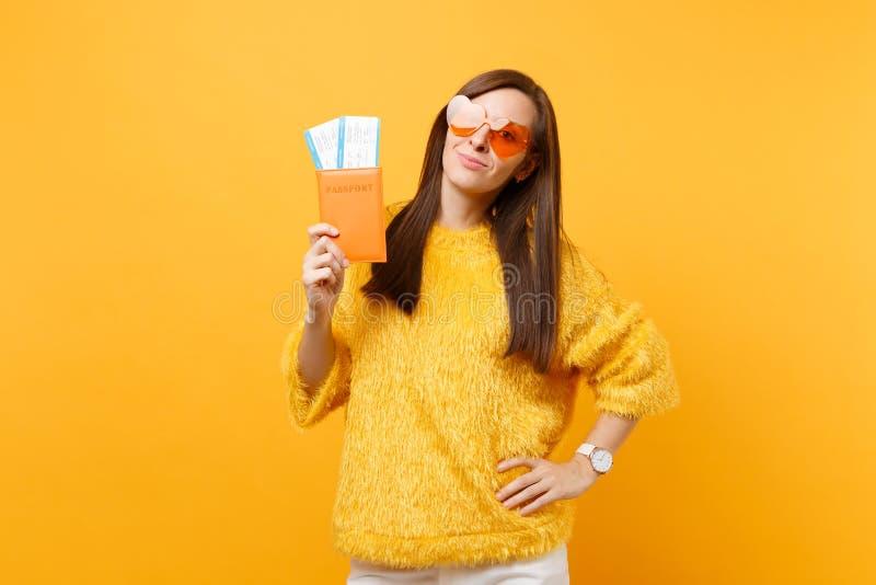 毛皮毛线衣、橙色心脏镜片持护照的和被隔绝的登机牌票的可爱的年轻女人  库存照片