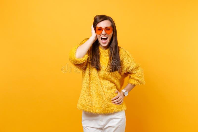 毛皮毛线衣、白色裤子和保留手的心脏橙色玻璃的激动的愉快的少女在明亮隔绝的头附近 免版税库存照片