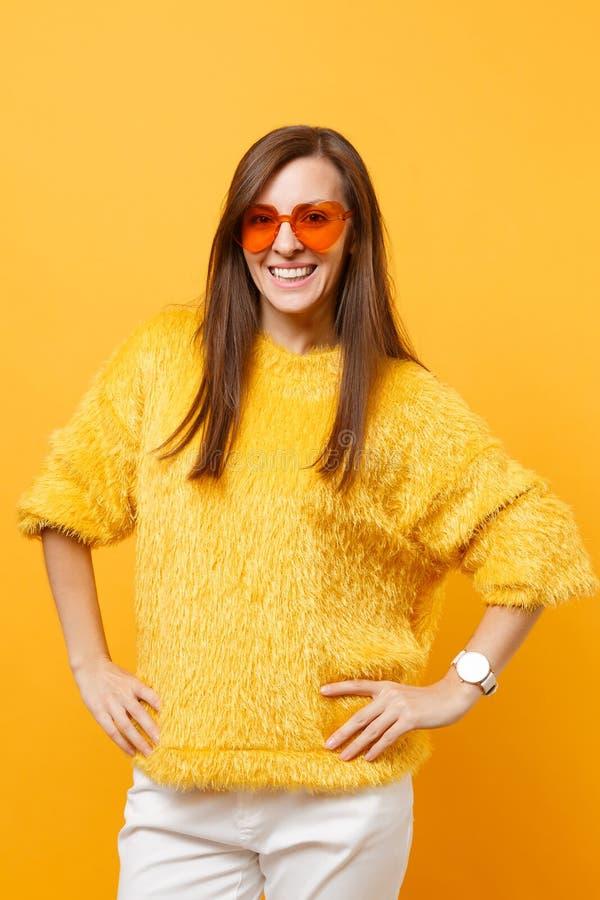 毛皮毛线衣、白色裤子和站立与胳膊两手插腰的心脏橙色玻璃的微笑的年轻女人隔绝在明亮 免版税库存图片