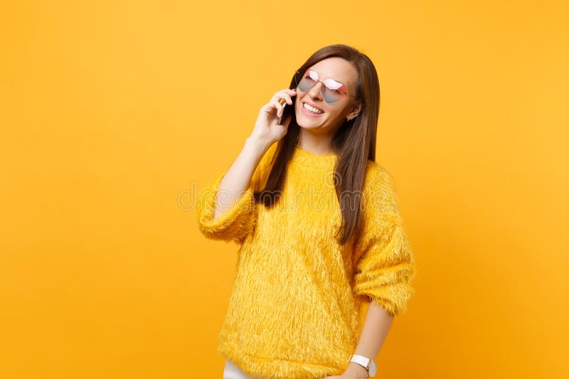 毛皮毛线衣的,心脏玻璃美丽的年轻女人谈话在举办宜人的交谈的手机被隔绝  免版税库存照片